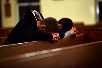 Two men pray at Saint Rose of Lima Roman Catholic Church near Sandy Hook Elementary School, where a gunman opened fire on school children and staff in Newtown