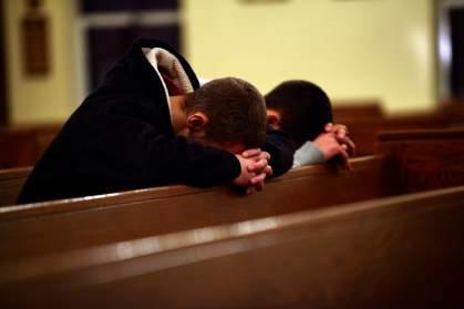 Two men pray at Saint Rose of Lima Roman Catholic Church near Sandy Hook Elementary School, where a gunman opened fire on school children and staff in Newtown